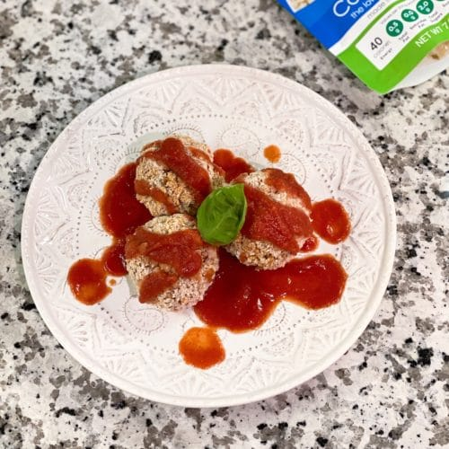 3 baked cauliflower rice balls drizzled with tomato sauce, topped with basil on a white plate
