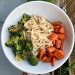 white bowl with charred broccoli, carrots, and pasta topped with red chili flakes