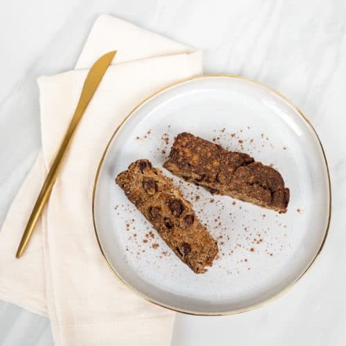 Two slices of cinnamon raisin banana bread on a white gold plate with a linen napkin and gold knife