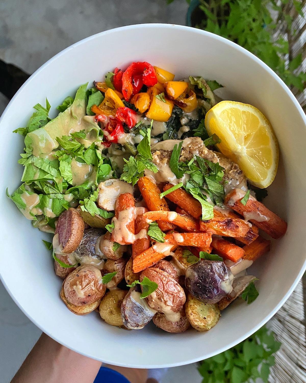 Easy Vegan Buddha Burger Bowl in white bowl with fresh greens, yellow lemon, orange carrots, purple potatoes, and cilantro garnishes
