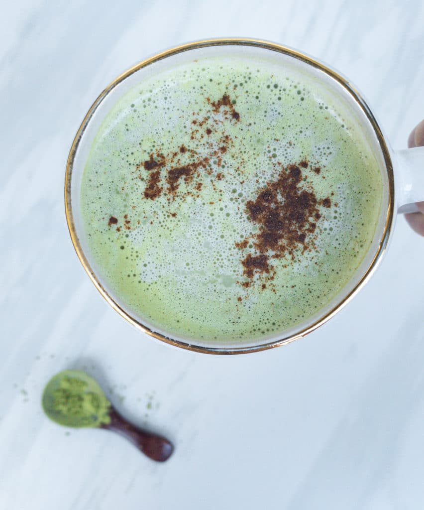 Close-up of vegan mint green matcha latte in white mug on white marble surface. Brown wooden spoon with matcha powder.