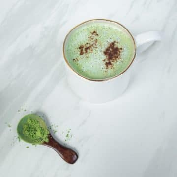 Vegan mint green matcha latte in white mug on white marble surface. Brown wooden spoon with matcha powder.