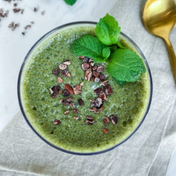 Bright green mint chocolate smoothie from overhead with mint leaves