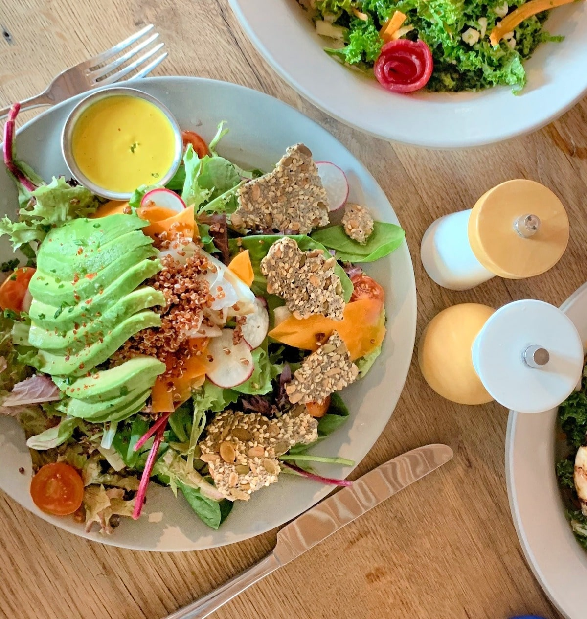 Healthy food choice at restaurant - salad on a gray plater with lettuce, avocado, crackers, and yellow dressing.