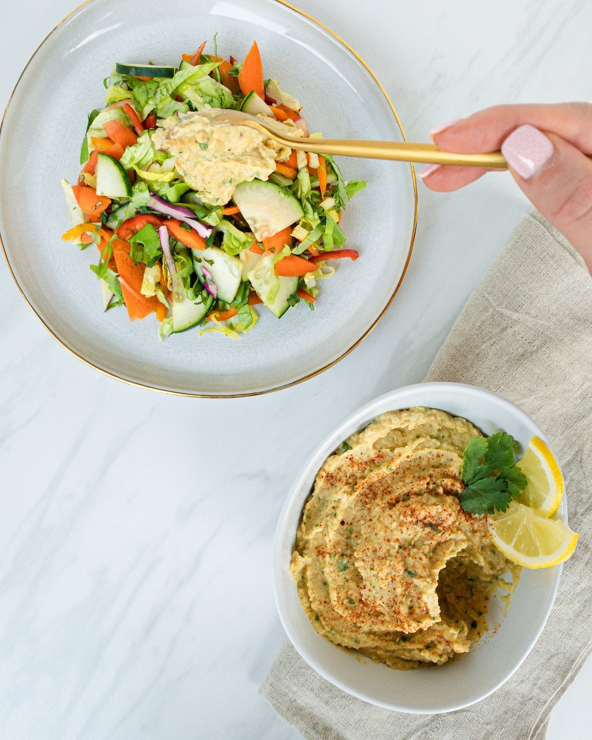 Oil-free hummus in white bowl with cilantro and lemon, on gray napkin. Bright salad on plate to left, gold spoon scooping hummus onto salad.