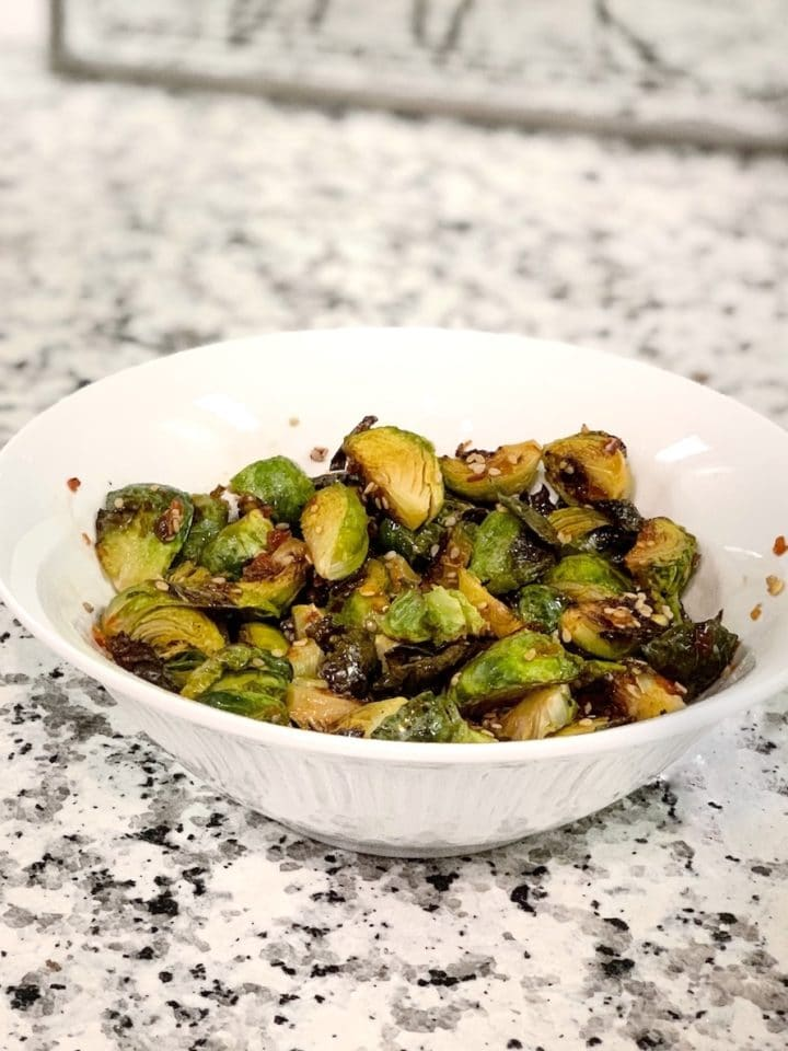 Asian maple glazed brussel sprouts in a white bowl on a marble counter.