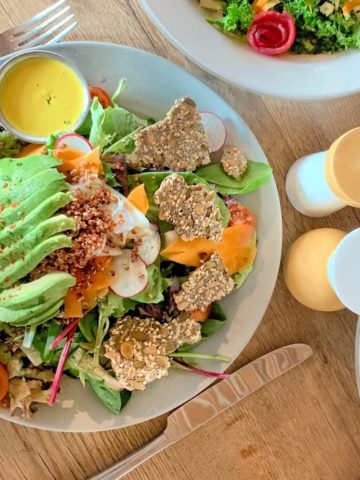 Salad on a gray plater with lettuce, avocado, crackers, and yellow dressing.