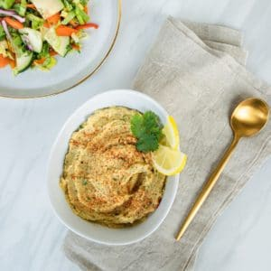 Oil-free hummus in white bowl with cilantro and lemon, on gray napkin with gold spoon. Bright salad on plate to left.