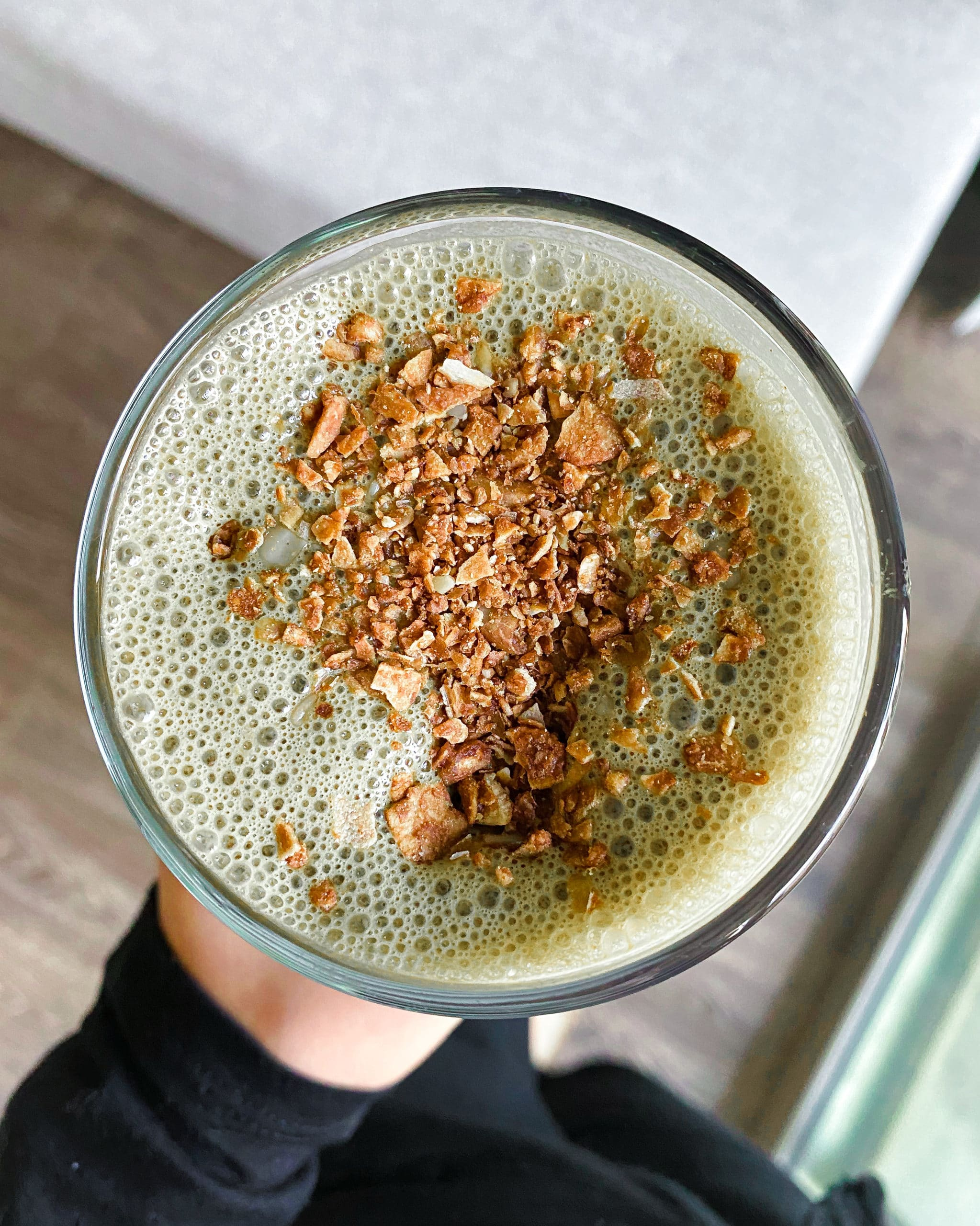 Nutty buddy green smoothie in a glass with chocolate granola on top.