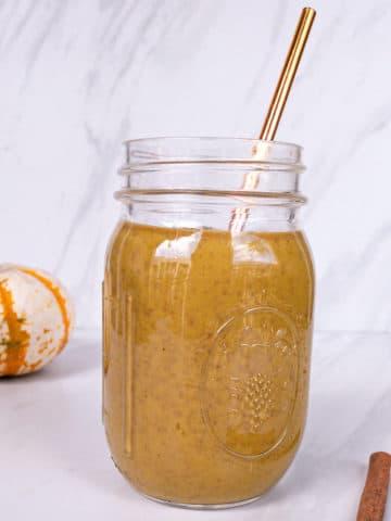 Pumpkin Pie smoothie in mason jar with cinnamon sticks and pumpkin