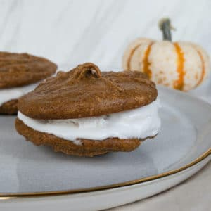 Side angle of whoopie pie on plate with pumpkin in background