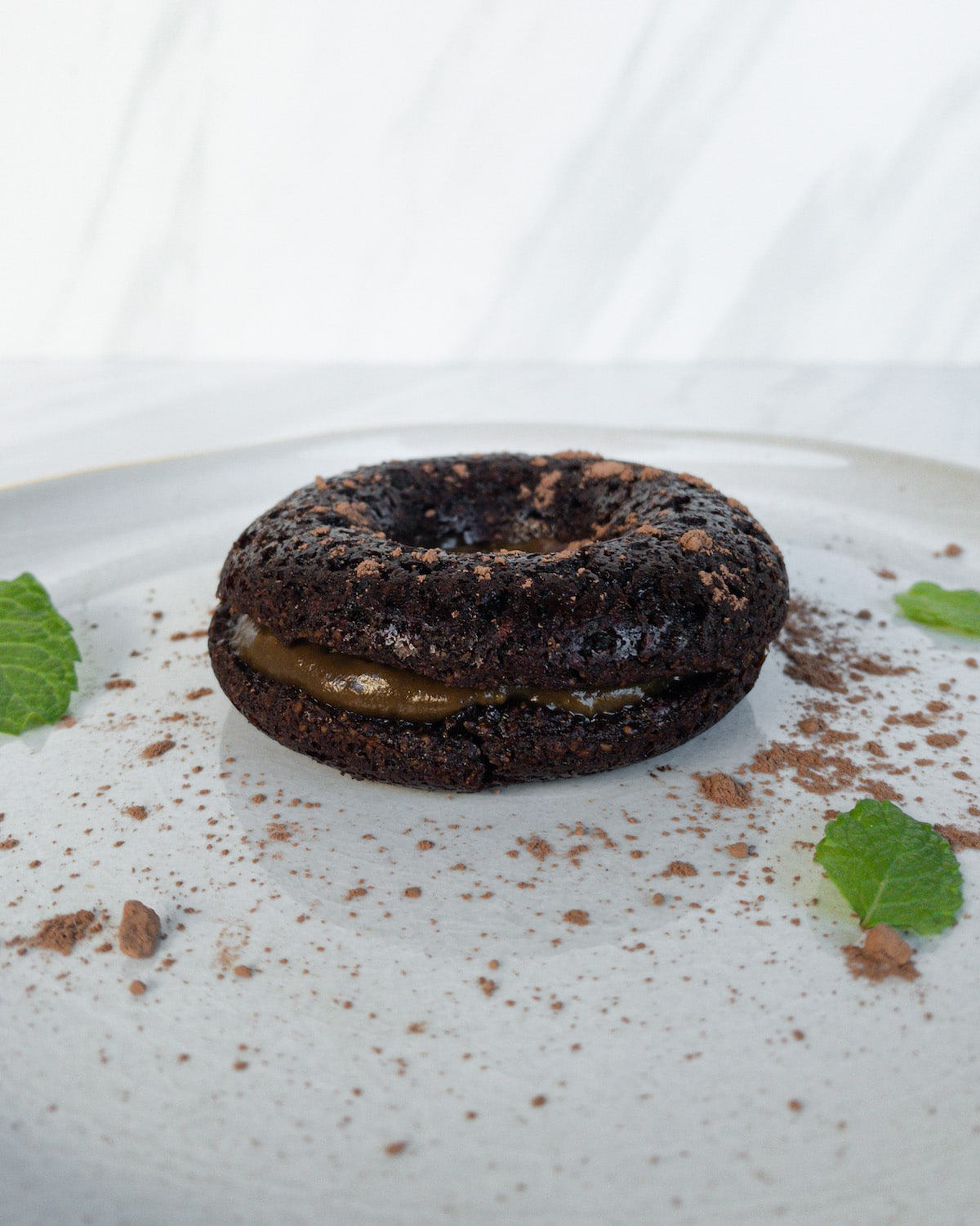 side angle of donut on plate with mint leaves