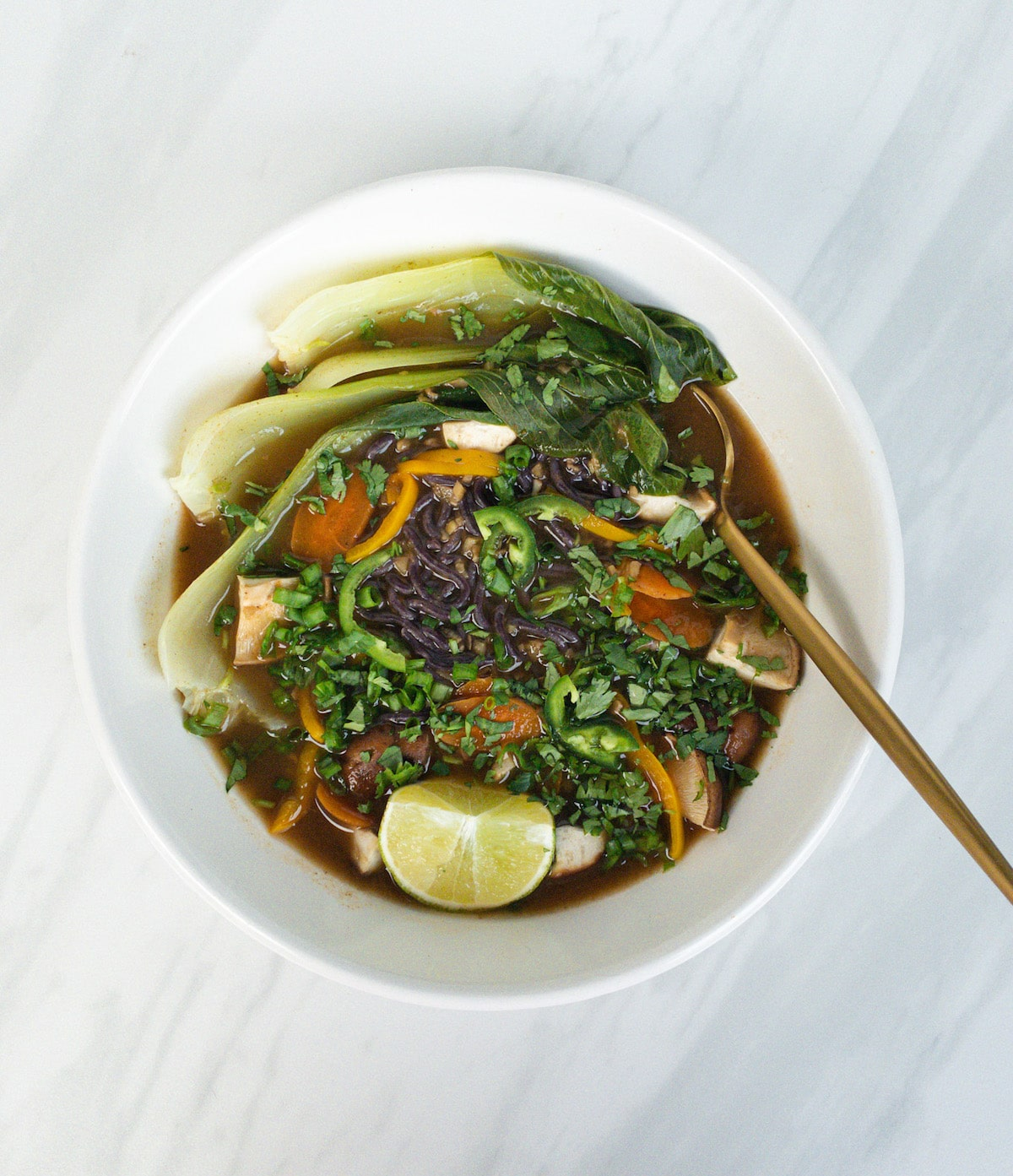 overhead view of vegan pho with vegetables in white bowl with gold spoon