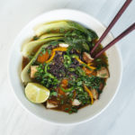 overhead view of vegan pho with vegetables in white bowl with chopsticks