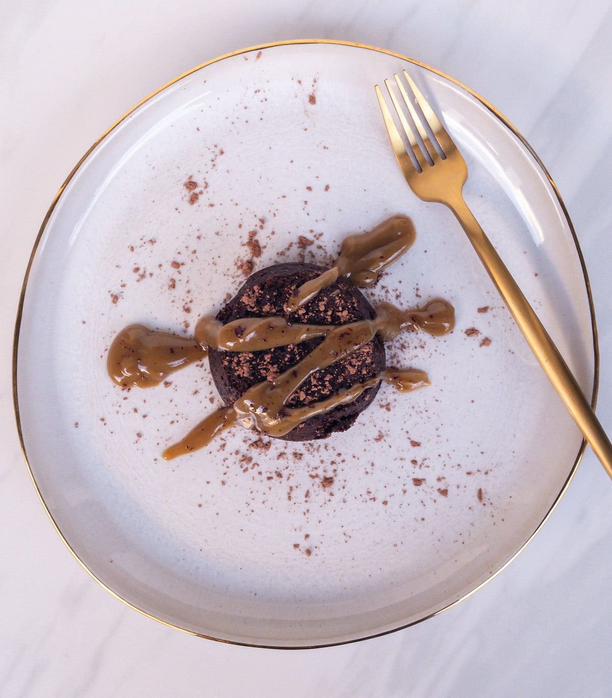 chocolate lava cake on white plate with golden drizzle and fork