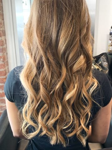 back of woman's head curled brunette hair with blonde highlights