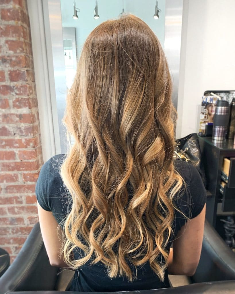 back of girl's head curled brunette hair with blonde highlights