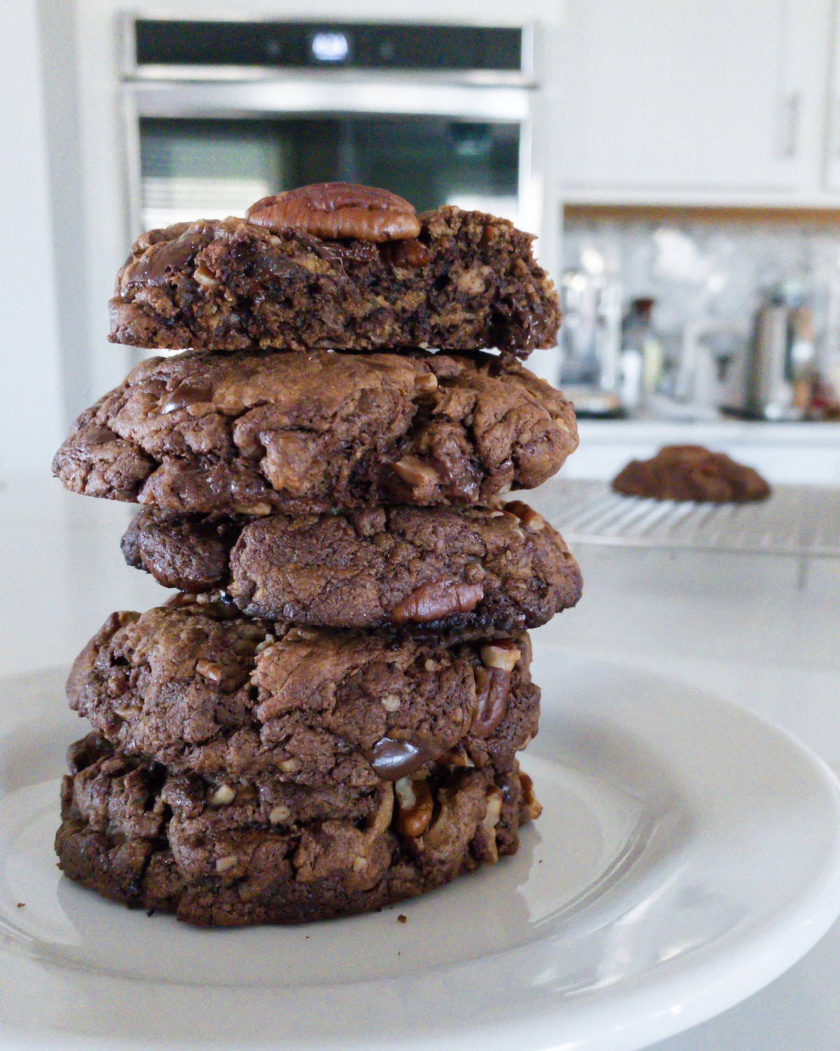 Stack of brown cookies on white plate