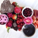 Pink, red, and brown charcuterie board filled with fruit and chocolate.