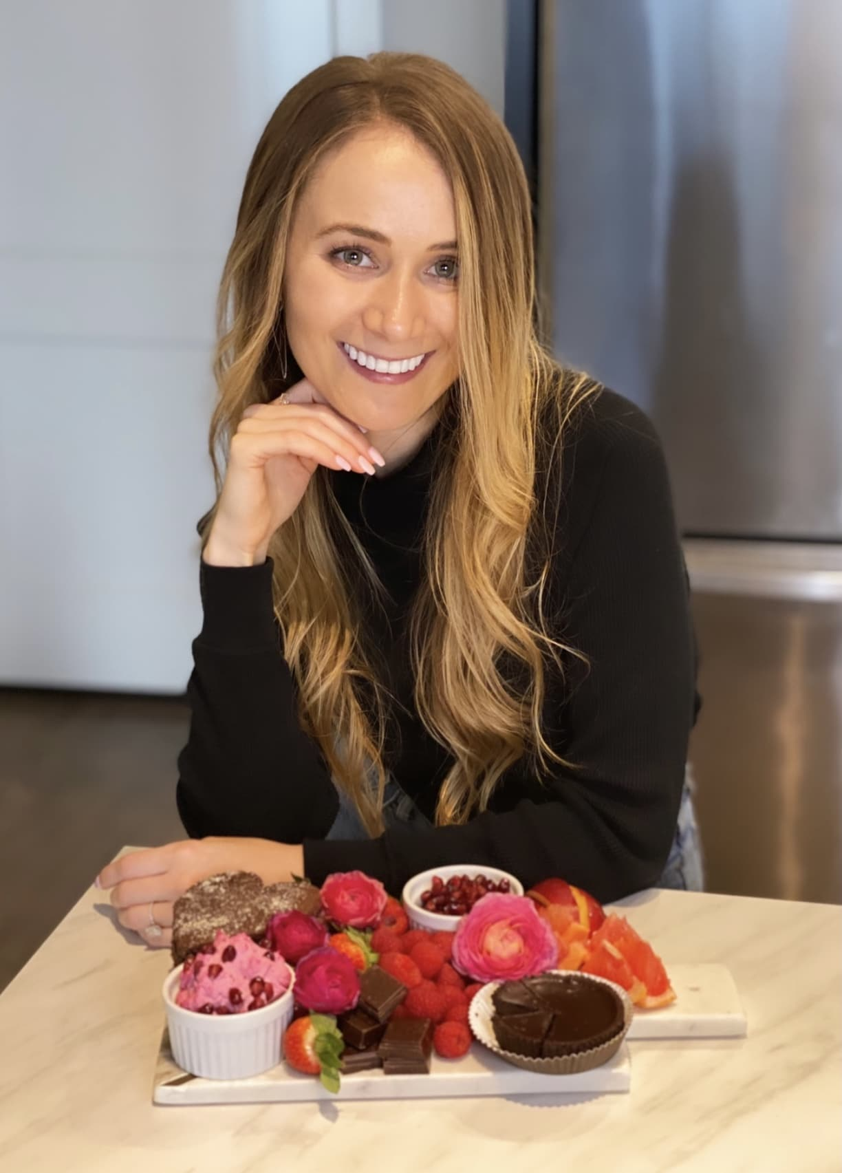 Girl smiling with pink, red, and brown charcuterie board filled with fruit and chocolate.
