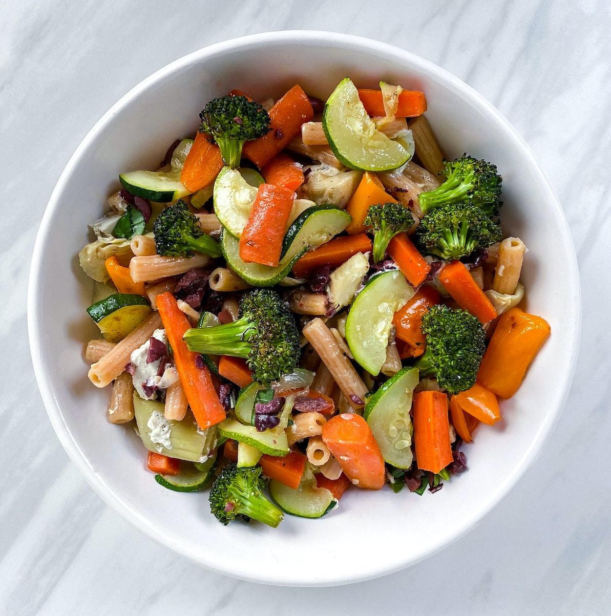 Bright pasta primavera with carrots, broccoli, and veggies in a white dinner bowl