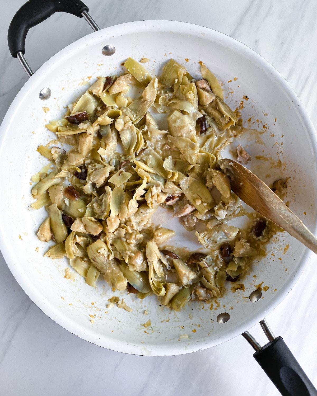 Pasta primavera sauce cooking in a white pan