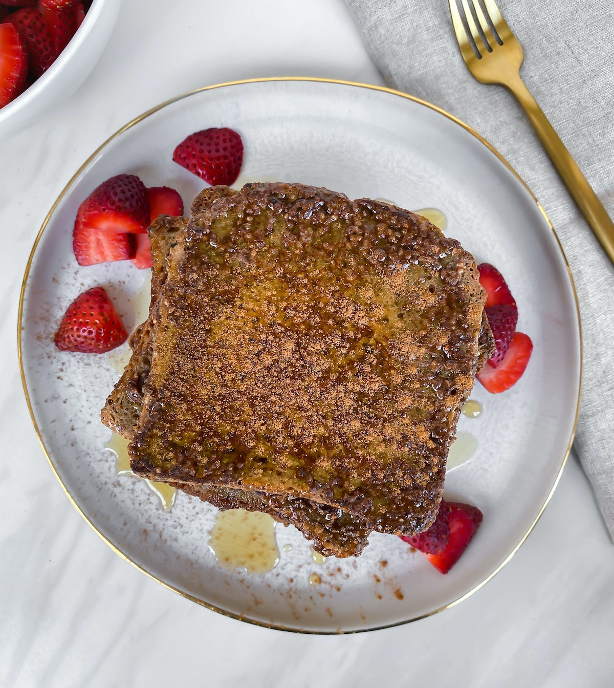 Healthy vegan gluten free golden brown french toast with bright red strawberries
