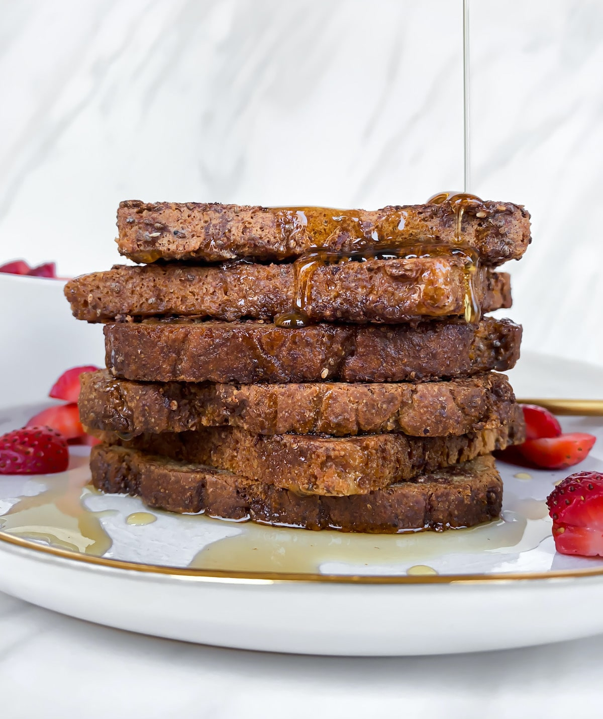 Side view of a stack of healthy vegan gluten free golden brown french toast with bright red strawberries and syrup pour