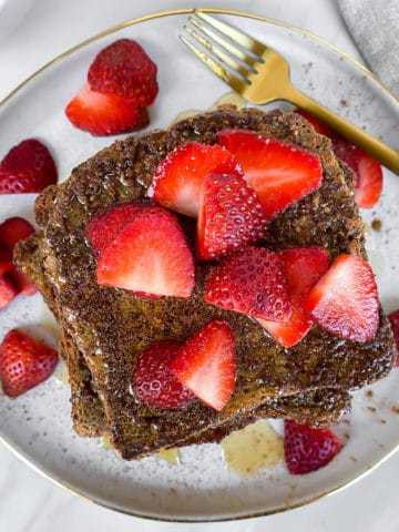 Healthy vegan gluten free golden brown french toast with bright red strawberries on top