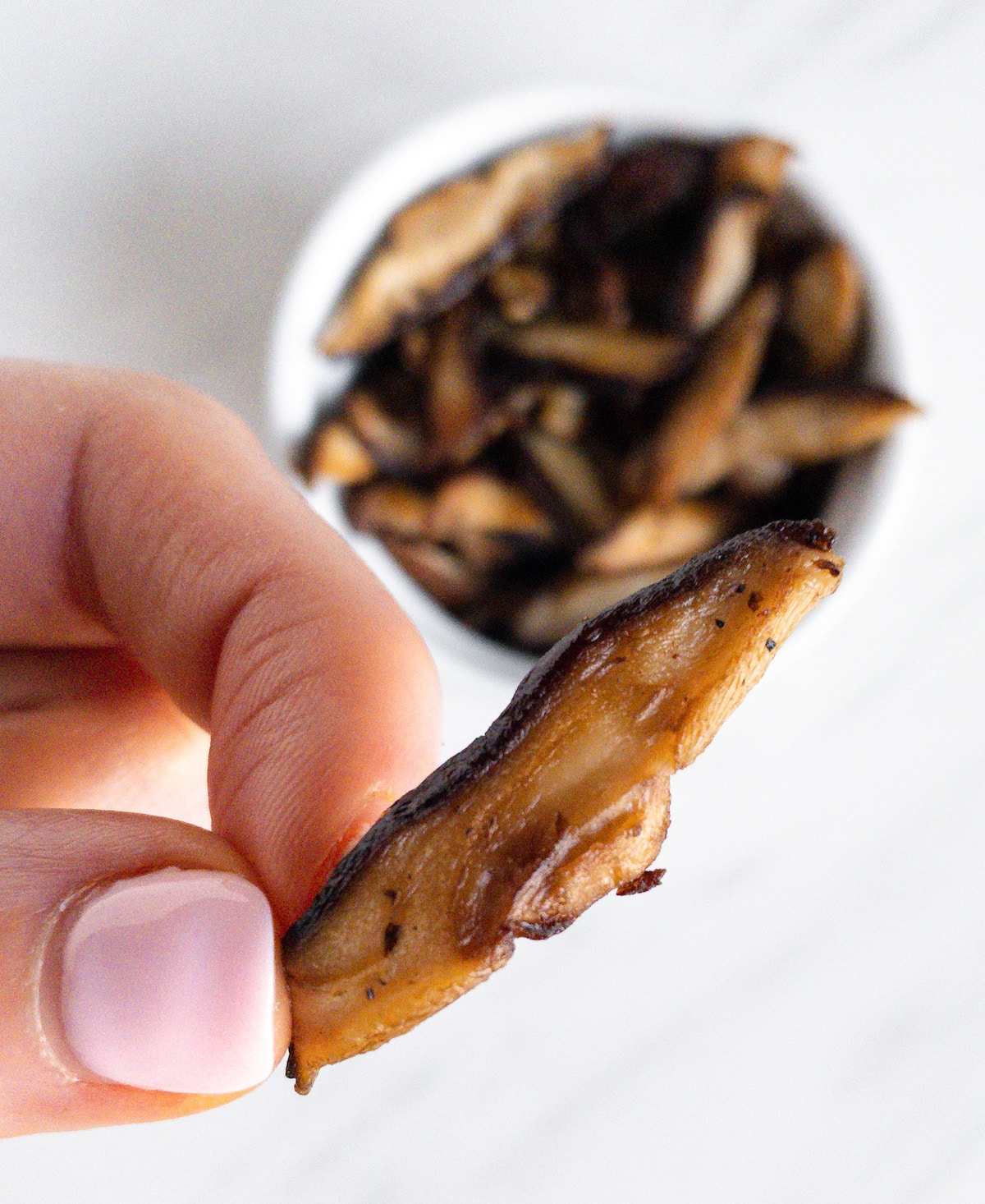 Holding a piece of vegan mushroom bacon
