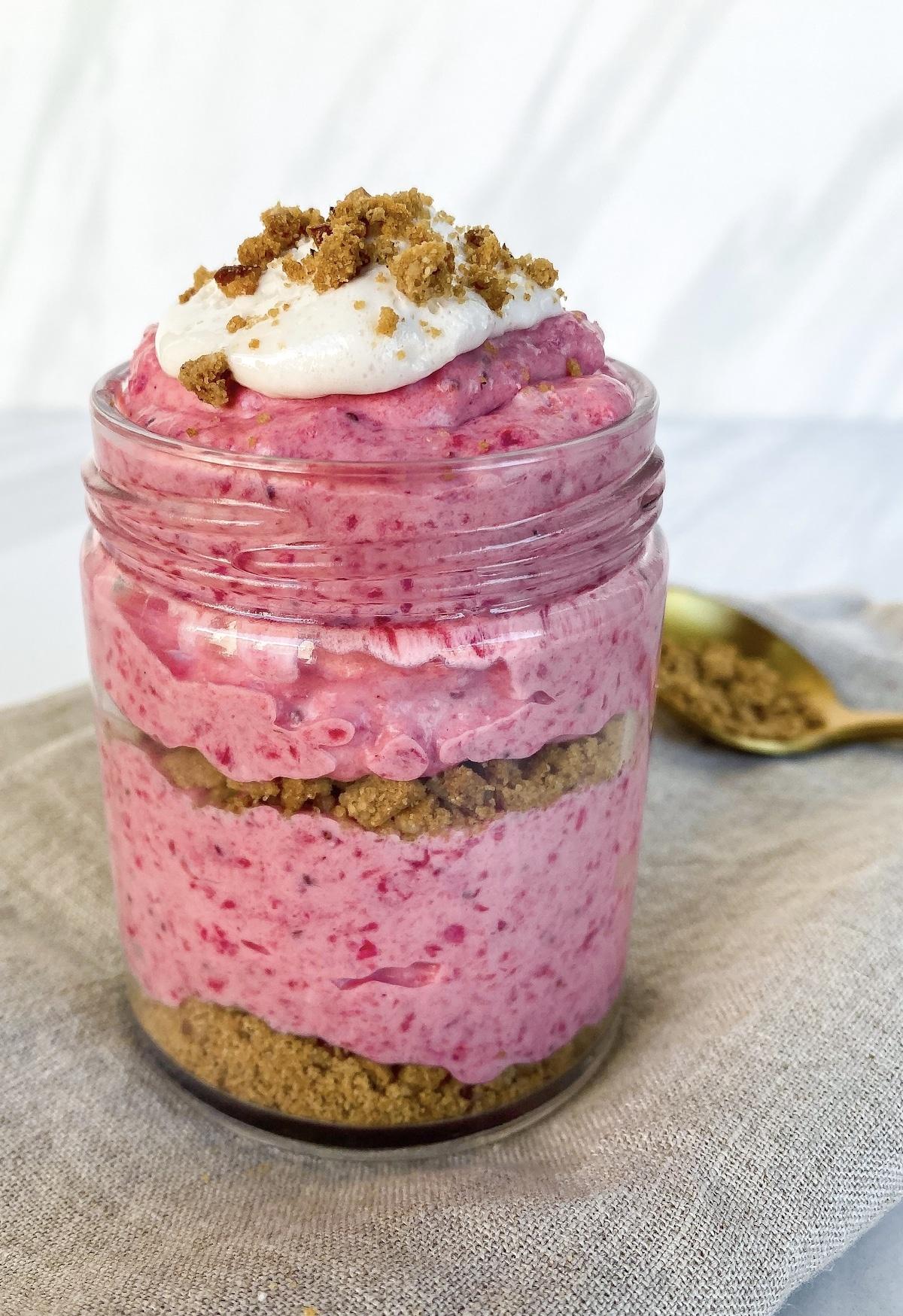 Layered strawberry cheesecake dessert in a glass jar