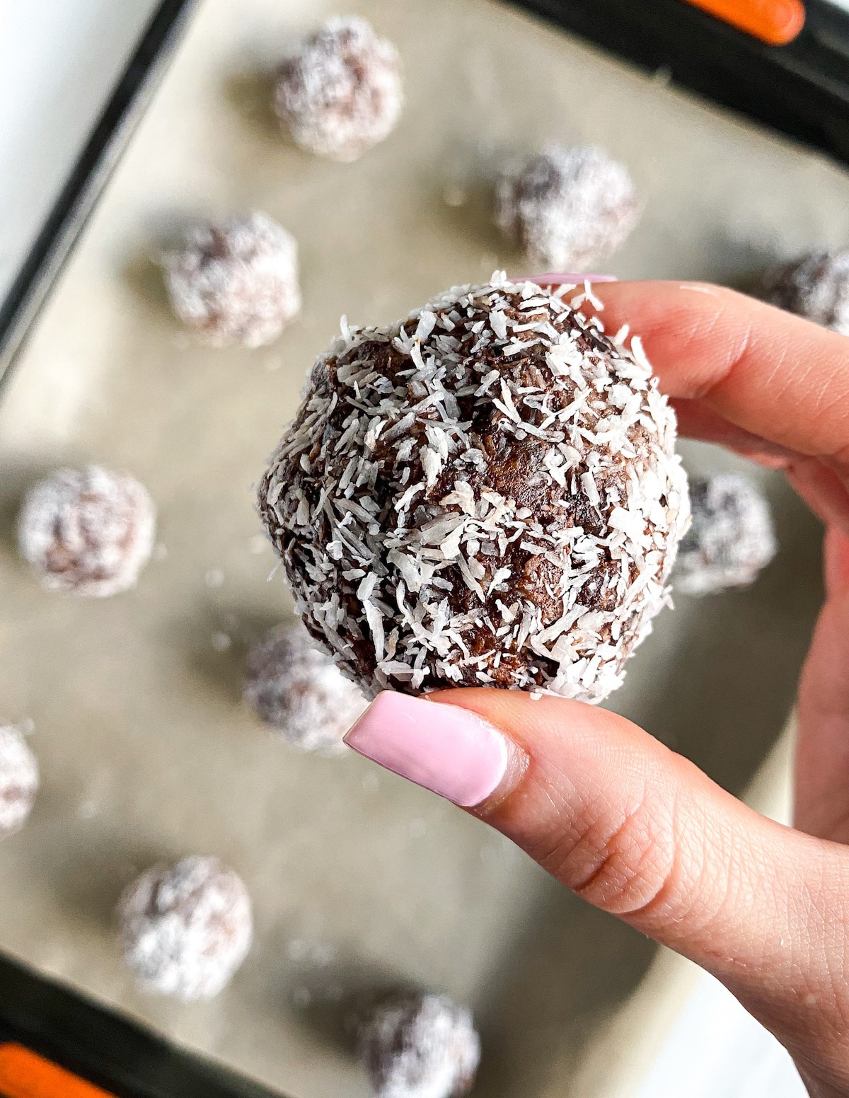 Holding a energy ball in front of a tray of energy balls