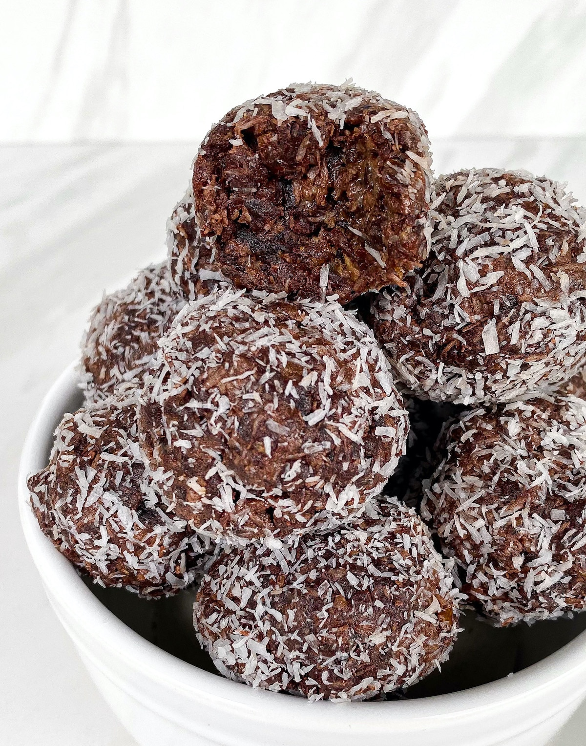 Bowl of healthy cocoa energy balls with a bite taken out
